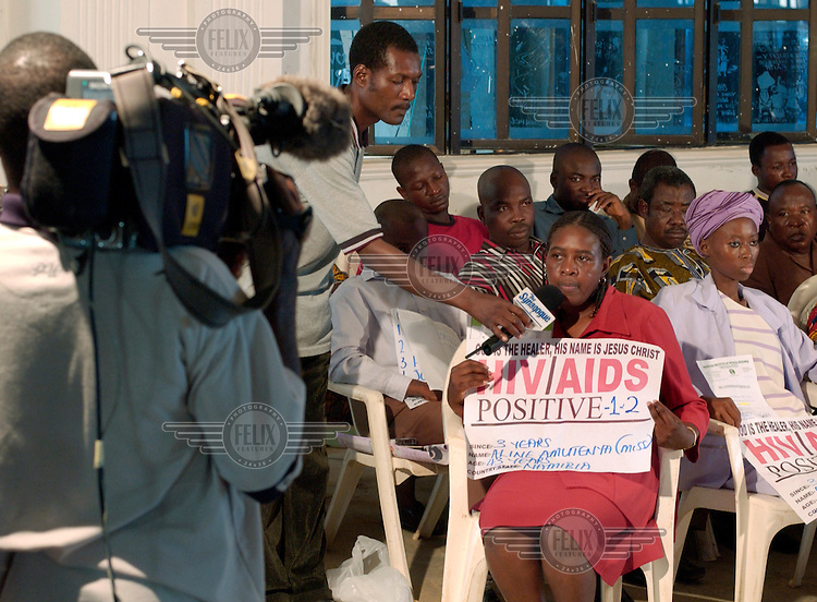 Parishioners give testimony into a microphone so that as many as 5,000 people can watch on television screens at The Synagogue Church of All Nations after Pastor T.B. Joshua 'cured' them of HIV/AIDS. People come to the church from all over Africa to be cured of evils such as AIDS, cancer and infertility.