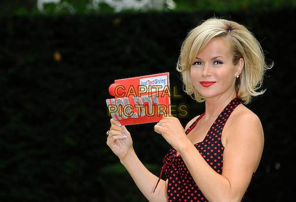 Amanda Holden.Photocall for Vodafone JustTextGiving Charity Challenges, London, England..5th September 2011.half length black red dress polka dot halterneck sign lipstick .CAP/CJ.©Chris Joseph/Capital Pictures.