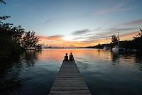 Honduras, Roatan Island, Fantasy Island Resort, Caribbean. Man and woman talking on dock at sunset.