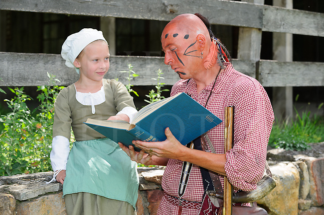 Native American Indian reenactor attmpting to read a book with a young little girl helping.
