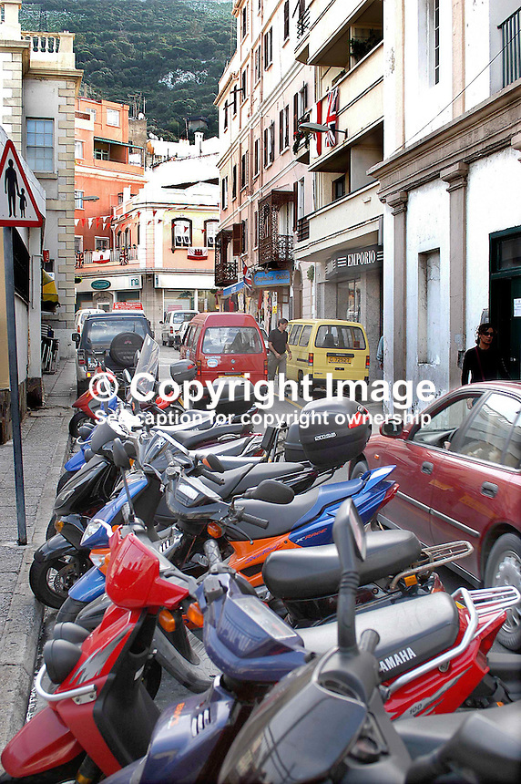 Narrow street in Gibraltar lined with mopeds. Ref: 200211041176...Copyright Image from Victor Patterson, 54 Dorchester Park, Belfast, UK, BT9 6RJ..Tel: +44 28 9066 1296.Mob: +44 7802 353836.Voicemail +44 20 8816 7153.Skype: victorpattersonbelfast.Email: victorpatterson@mac.com.Email: victorpatterson@ireland.com (back-up)..IMPORTANT: If you wish to use this image or any other of my images please go to www.victorpatterson.com and click on the Terms & Conditions. Then contact me by email or phone with the reference number(s) of the image(s) concerned.