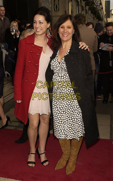 """ARLENE PHILLIPS & GUEST.Outside arrivals for """"Movin' Out"""" Opening Night, .Apollo Victoria Theatre, London, England, .April 10th 2006..full length black and white print dress waving hand.Ref: CAN.www.capitalpictures.com.sales@capitalpictures.com.©Can Nguyen/Capital Pictures"""