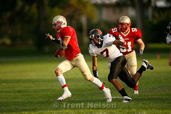 Salt Lake City - Judge quarterback Daniel Shiramizu, pursued by Ogden's Danzel Swinton. Judge vs. Ogden high school football Friday, August 28 2009, played at Granite High School. .
