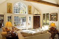 Traditional style white walled llivingroom with wooden barn beam, sailboat model, overstuffed sofa and chairs.