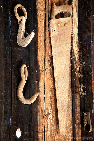 Still life of old saw and hooks in blacksmith shop