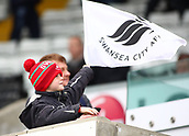 17th March 2018, Liberty Stadium, Swansea, Wales; FA Cup football, quarter-final, Swansea City versus Tottenham Hotspur; Young Swansea City fan holds a team flag before kickoff
