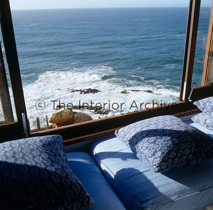 Blue cushions line the window seat in the living room which has dramatic views over Plettenberg Bay