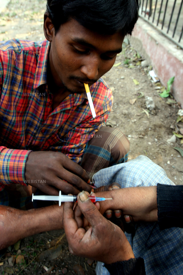 2006. Bangaldesh, Dhaka. Users aid each other with their pathedrine injection. Pathedrine is a widely available pain-killer used as a drug...2006. Bangaldesh, Dhaka. Des consommateurs s'entreaident avec leur injection de pathedrine, un anti douleur très répandu utilisé comme drogue..