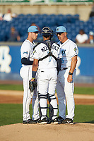Wilmington Blue Rocks pitching coach Steve Luebber (46) has a meeting on the mound with starting pitcher Daniel Tillo (43) and catcher MJ Melendez (7) during the game against the Fayetteville Woodpeckers at Frawley Stadium on June 6, 2019 in Wilmington, Delaware. The Woodpeckers defeated the Blue Rocks 8-1. (Brian Westerholt/Four Seam Images)
