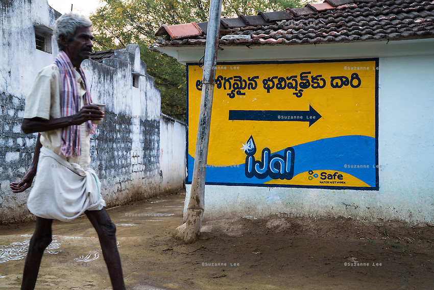 An man holds a cup as he walks past an iJal direction sign towards the iJal water station in Peddapur, a remote village in Warangal, Telangana, India, on 22nd March 2015. Safe Water Network works with local communities that live beyond the water pipeline to establish sustainable and reliable water treatment stations within their villages to provide potable and safe water to the communities at a nominal cost. Photo by Suzanne Lee/Panos Pictures for Safe Water Network