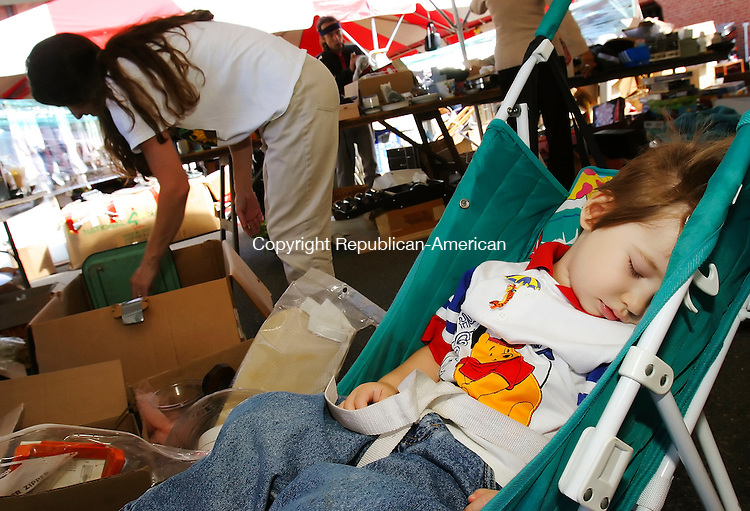 NAUGATUCK,  CT 09 September 2005 -090905BZ02- Conner Perry (CQ), 2, of Beacon Falls, sleeps soundly while his mother Jenny Perry looks through articles for sale in the &quot;white elephant tent&quot; during the annual St. Michael's Church Fair on the green Friday afternoon. <br />  Jamison C. Bazinet / Republican-American