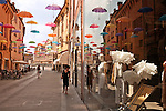 Colorful umbrellas, an open art installation over Via Mazzini, a shopping street in the Historic Old Town with the Cathedral in the background