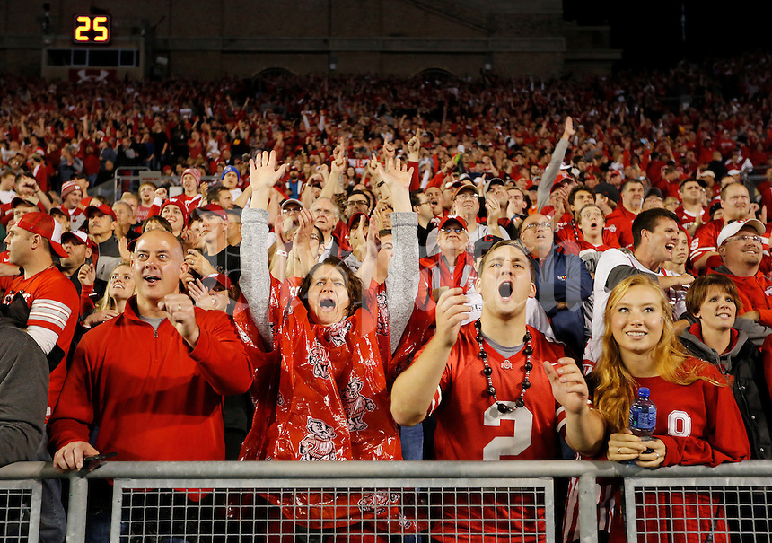 From left, Wisconsin fans Mike and Brenda Hawley of Eden Prarie, Minn., and Ohio State alums Stephen Eifert of Columbus and Regina Gallagher of Madison, Wisc. have different reactions to an instant replay review of a fumble during the first quarter of the NCAA football game at Camp Randall Stadium in Madison, Wisconsin on Oct. 15, 2016. (Adam Cairns / The Columbus Dispatch)