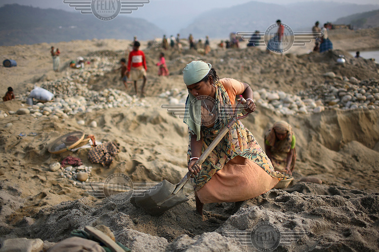 A labourer shovels sand. At least 10,000 people, including 2,500 women and over 1,000 children, are engaged in stone and sand collection from the Bhollar Ghat on the banks of the Piyain river. Building materials such as stone and sand, and the cement which is made from it, are in short supply in Bangladesh, and commands a high price from building contractors. The average income is around 150 taka (less than 2 USD) a day...