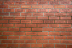 A red brick wall of fame with supporters names inside the stadium, pictured before Greenock Morton take on Stranraer in a Scottish League One match at Cappielow Park, Greenock. The match was between the top two teams in Scotland's third tier, with Morton winning by two goals to nil. The attendance was 1,921, above average for Morton's games during the 2014-15 season so far.