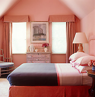 Pink is not necessarily girly as this rose-tinted bedroom shows where it is used from the distressed finish of the chest-of-drawers to the bedding, pelmet and curtains