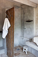 The walk-in shower area of this stone-walled bathroom has been covered in a layer of concrete with a rustic shutter used as a partition wall