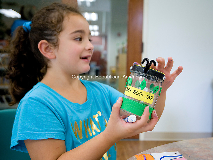 MIDDLEBURY, CT-080817JS02-- Gianna DeLorenzo, 7, of Middlebury, shots off her decorated bug jar she made during the summer reading camp craft program Tuesday at the Middlebury Public Library. Jim Shannon Republican-American