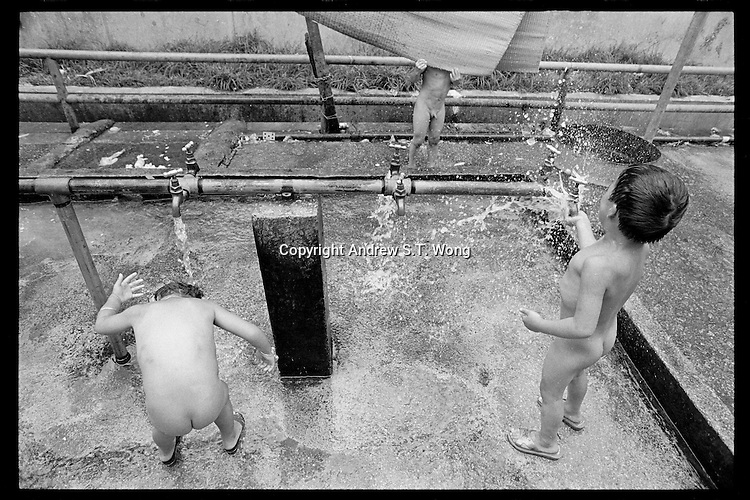 Vietnamese refugee boys play with water at a boat people camp in Hong Kong. Tens of thousands of Vietnamese refugees fled the Communist regime by boats to Hong Kong in 1980s.