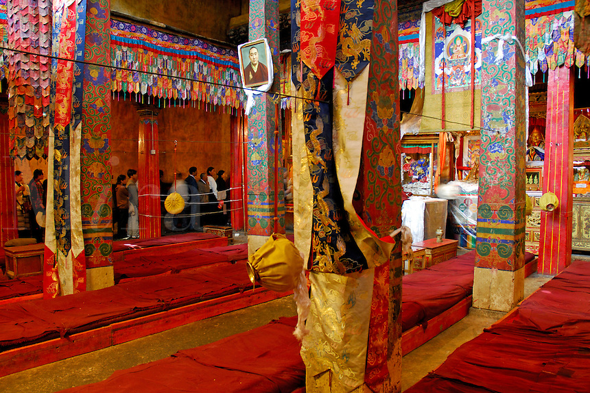 Buddhist pilgrims line up to light butter lamps and pray, moving clockwise through Ramoche Temple, with silk adorned columns in the main hall, built in the 7th century, sister to the Jokhang Temple, Lhasa, Tibet, China.