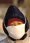 Chinese girl wearing anti-pollution mask against the cold and traffic fumes