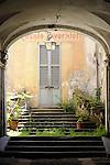 Archway with a few plants, and an old store sign painted above a pale blue door in Bellano, a town on Lake Como, Italy.
