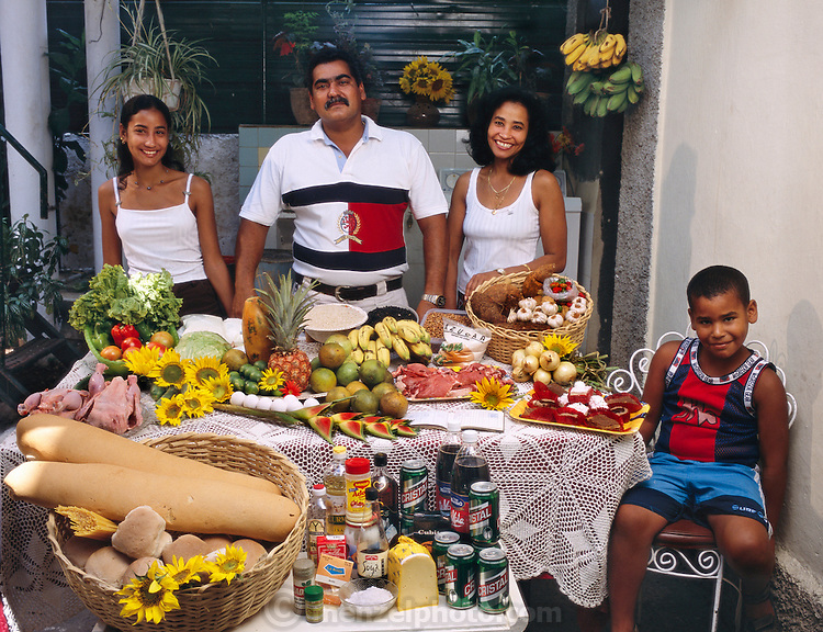 (MODEL RELEASED IMAGE). In a rare moment, when not surrounded by the in-laws and cousins with whom they share a Colonial-era house, the Costa family?Ramon Costa Allouis, 39, Sandra Raymond Mundi, 38, and their children Lisandra, 16, and Fabio, 6?in the courtyard of their extended family's home in Havana, Cuba with one week's worth of food. Cooking methods: indoor gas stove, outdoor homemade BBQ grill. Food preservation: refrigerator, grandfather's freezer chest in the courtyard. /// The Costa family is one of the thirty families featured in the book Hungry Planet: What the World Eats (p. 96). Food expenditure for one week: $56.76 USD. (Please refer to Hungry Planet book p. 97 for the family's detailed food list.)