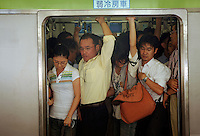 Comutors squeeze onto trains in Shinjuku station, Tokyo, Japan..03 Sep 2008