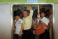 Comutors squeeze onto trains in Shinjuku station, Tokyo, Japan..03 Sep 2008