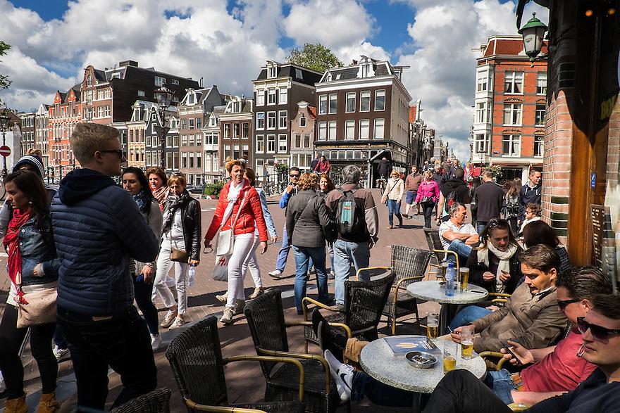 Nederland, Amsterdam, 30 mei 2015<br /> Terras van een amsterdame kroeg op de hoek van een gracht. Drommen toeristen lopen langs op weg naar het Rijksmuseum. <br />  <br /> Foto: Michiel Wijnbergh