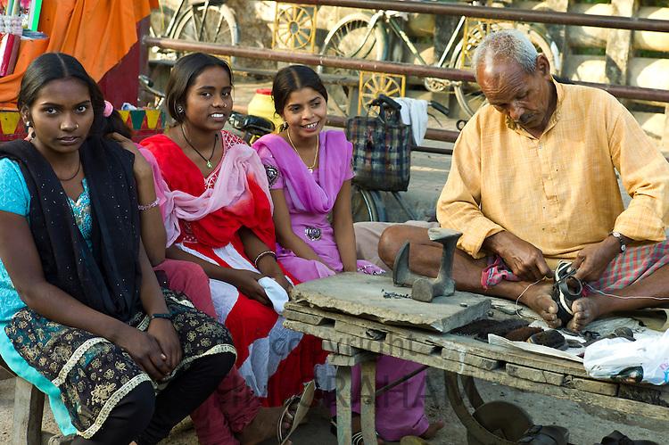 Indian girls in shoe shop with cobbler at work at Sarnath near Varanasi, Benares, Northern India