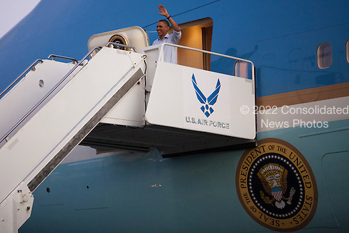United States President Barack Obama waves as he disembarks from Air Force One at Joint Base Pearl Harbor-Hickam in Honolulu, Hawaii, Friday, December 23, 2010. President Obama joins First Lady Michele Obama and daughters Sasha and Malia in Hawaii for the winter holidays..Credit: Kent Nishimura / Pool via CNP