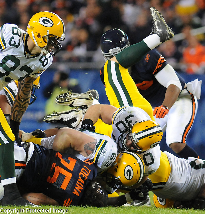 Green Bay Packers fullback John Kuhn, right, rolls over teammate Scott Wells (63) during a rush against the Chicago Bears during the game at Soldier Field on Monday, Sept. 27, 2010.