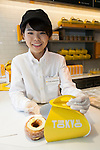 A member of staff shows a Cronut during the pre-opening event for the new pastry shop ''Dominique Ansel Bakery'' in Omotesando Hills on June 17, 2015, Tokyo, Japan. The new brand is known for its Cronuts pastry; a croissant doughnut fusion creation by Chef Dominique Ansel and is already hugely popular in New York. This is the first time that it will open an international branch. Japan has seen a recent boom in international food retailers especially trying to become the latest new trend in Tokyo. The store opens its doors to the public on June 20th and long lines are expected. (Photo by Rodrigo Reyes Marin/AFLO)