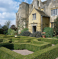 A formal parterre leads to the front entrance of the house