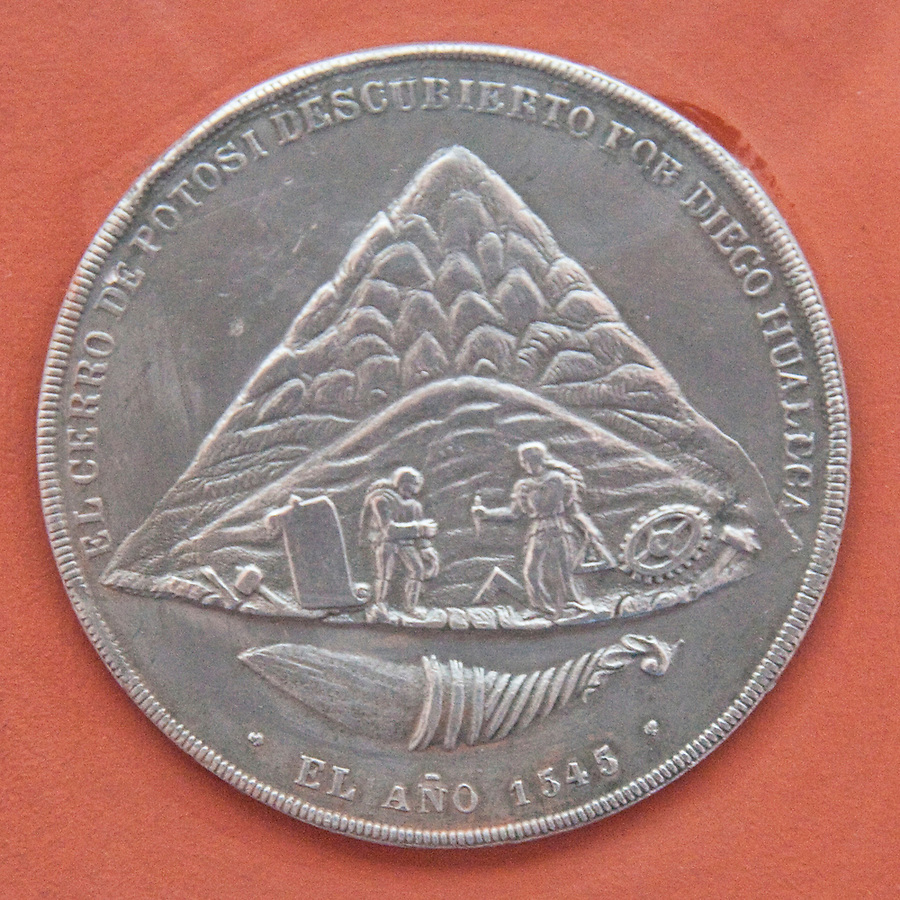 A silver coin minted in Potosí in 1545.  The image depicts the discovery of the mountain's riches by the indian Diego Huallpa.