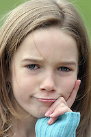 A young girl looks quizically at the camera.