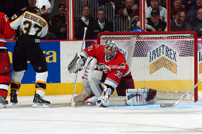 Carolina Hurricanes' goaltender Cam Ward makes a save watched by the  Boston Bruins' Patrice Bergeron during their game at the RBC Center in Raleigh, NC Wednesday, March 1, 2006. The Hurricanes won 4-3...