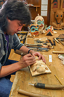 Native artist Tommy Joseph carves Tlingit artwork at the Sitka National Historic Park in Sitka, Alaska