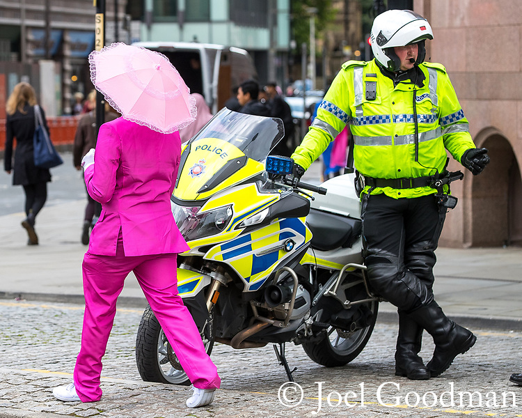 © Joel Goodman - 07973 332324. 30/07/2017 . Manchester , UK . A man dressed in a pink suit and carrying a pink umbrella walks passed a motorcycle policeman who is watching over crowds at the venue . Cosplayers, families and guests at Comic Con at the Manchester Central Convention Centre . Photo credit : Joel Goodman