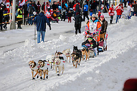 Kim Franklin runs down 4th avenue during the Ceremonial Start of the 2016 Iditarod in Anchorage, Alaska.  March 05, 2016