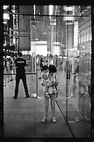 A woman uses an iPhone as she holds her toddler daughter outside an Apple shop in Shanghai, China, August, 2012. (Leica M6, 50mm f2, Kodak TRI-X 400)