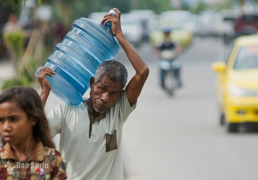 A man carries a 5-gallon bottle of water on  a busy street in Dili, Timor-Leste (East Timor)