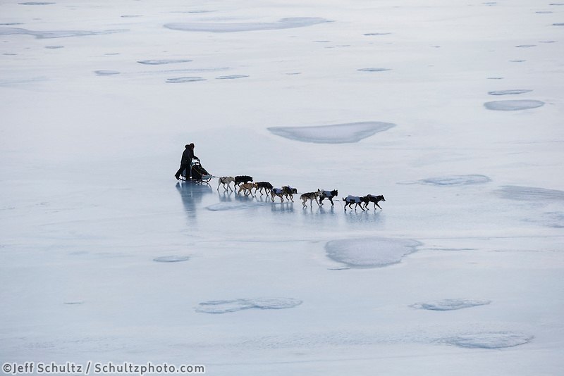 Ray Redington Jr. on the Golovin Bay sea ice nearing Golovin on Monday, March 10, during the Iditarod Sled Dog Race 2014.<br /> <br /> PHOTO (c) BY JEFF SCHULTZ/IditarodPhotos.com -- REPRODUCTION PROHIBITED WITHOUT PERMISSION