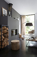 The focus of the contemporary living area is a minimal fireplace painted the same dark grey as the wall behind it