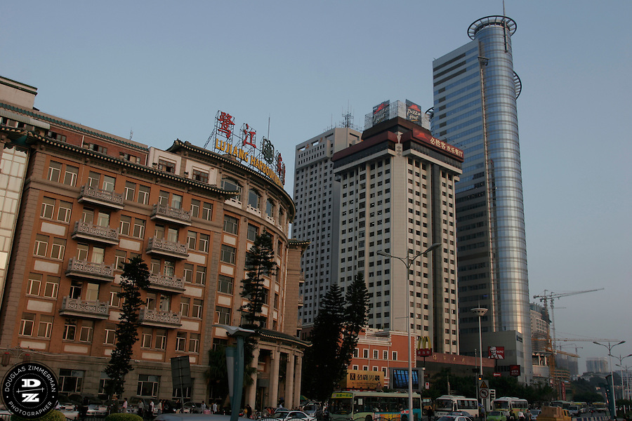 A mixture of old and new skyscrapers create the skyline along the waterfront of Xiamen, China.   Photograph by Douglas ZImmerman