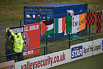 A steward helping a supporter of Irish club Bohemians tying flags behind the goal at Park Hall Stadium, Oswestry before their team's Champions League 2nd qualifying round 2nd leg game away to The New Saints. Despite leading 1-0 from the first leg, the Dublin club went out following their 4-0 defeat by the Welsh champions. The match was the first-ever Champions League match in the UK played on an artificial pitch and was staged at the Welsh Premier League's ground which was located over the border in England.