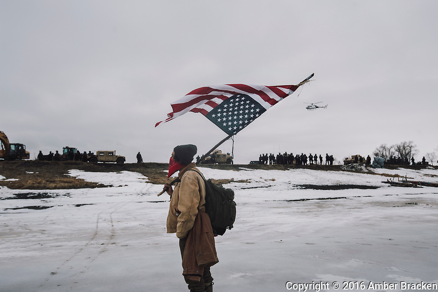A man watches from the river as police dismantle a crossing structure at the DAPL resistance camps near Cannon Ball, ND on Thursday, February 23, 2016. Police moved in to clear Oceti Sakowin, the largest of the camps. The eviction was peaceful, but police made at least 10 arrests.