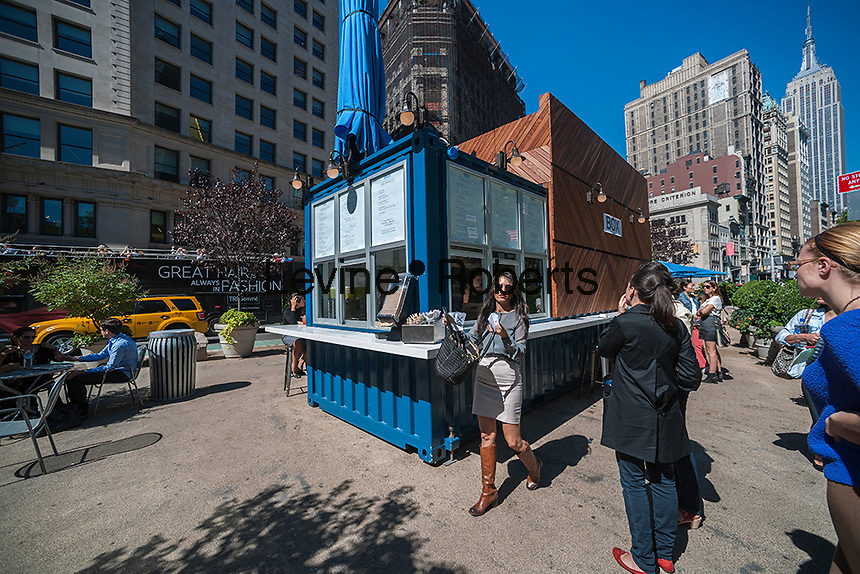 Customers pick up and place their orders at the new Ilili Box restaurant in Madison Square in New York on Wednesday, September 18, 2013. The kiosk, in a repurposed shipping container, was created by chef Philippe Massoud and serves traditional Middle-Eastern food as well as variations with Korean and Mexican twists.  (© Richard B. Levine)