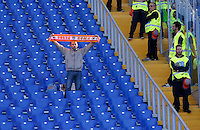 Calcio, Serie A: Roma vs Lazio. Roma, stadio Olimpico, 8 novembre 2015.<br /> A Roma fan holds his scarf  past stewards, in the Roma fans' curva Sud sector almost empty, due to a protest against security measurements, prior to the start of the Italian Serie A football match between Roma and Lazio at Rome's Olympic stadium, 8 November 2015.<br /> UPDATE IMAGES PRESS/Riccardo De Luca